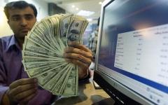 A man holds a plethora of hundred-dollar bills. (Photo credit: AAMIR QURESHI/AFP via Getty Images)