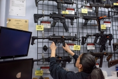 Employee Gorety Mejia takes down a HK MP5 for a customer at Full Armor Firearms store in Houston, Tex. (Photo credit: MARK FELIX/AFP via Getty Images)