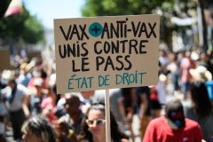 A protestor's placard makes the point that there are people with both pro- and anti-vaccination views who are united in opposition against the government's 'heath pass' mandate. (Photo by Clement Mahoudeau/AFP via Getty Images)