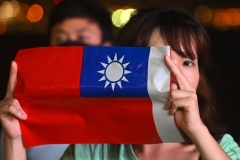 A woman holds a small Taiwanese national flag. (Photo by Philip Fong/AFP via Getty Images)