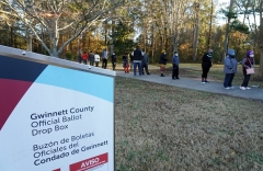 Behind the ballot drop box, voters wait in line to vote in person in Atlanta, Georgia. (Photo by TAMI CHAPPELL/AFP via Getty Images)