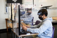 Students sit behind barriers and use tablets during an in-person English class at St. Anthony Catholic High School during the Covid-19 pandemic on March 24, 2021 in Long Beach, California. (Photo by PATRICK T. FALLON/AFP via Getty Images)