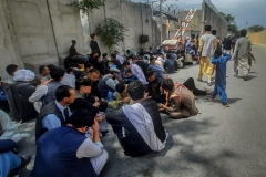 Afghan people sit outside the French embassy in Kabul on Aug. 17, 2021 waiting to leave Afghanistan. (Photo credit: ZAKERIA HASHIMI/AFP via Getty Images)