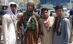 A Taliban fighter poses with locals after the group captured Pul-e-Khumri, the capital of Baghlan province, on Wednesday. (Photo by AFP via Getty Images)