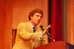 Tucker Carlson speaks from a podium during a Milton S. Eisenhower Symposium at Johns Hopkins University. (Photo credit: JHU Sheridan Libraries/Gado/Getty Images)