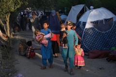 Internally displaced Afghan families, who fled from Kunduz, Takhar and Baghlan provinces due to battles between Taliban and Afghan security forces, walk past their temporary tents at Sara-e-Shamali in Kabul on August 11, 2021. (Photo by WAKIL KOHSAR/AFP via Getty Images)