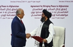 U.S. special representative for Afghanistan Zalmay Khalilzad and Taliban negotiator Abdul Ghani Baradar shake hands after signing the U.S.-Taliban agreement in Doha, Qatar in February 2020. (Photo by Karim Jaafar/AFP via Getty Images)