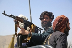Taliban fighters stand guard in a vehicle along the roadside in Kabul on August 16, 2021, after a swift end to the 20-year war, as thousands of people mobbed the city's airport trying to flee the group's feared hardline brand of Islamist rule. (Photo by AFP via Getty Images)