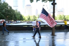Germano Riviera, a survivor of the Sept. 11, 2001 terrorist attacks in the city, carries a U.S. flag as he visits the National 9/11 Memorial & Museum on Sept. 10, 2021. (Photo credit: ROBERTO SCHMIDT/AFP via Getty Images)