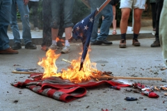 An American flag burns at a protest. (Photo credit: HIROKO MASUIKE/AFP via Getty Images)