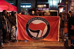 Antifa activists stand with a banner. (Photo credit: ZAKARIA ABDELKAFI/AFP via Getty Images)