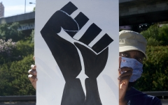 Featured is a poster with the Black Lives Matter fist at a protest. (Photo credit: Horacio Villalobos#Corbis/Getty Images)