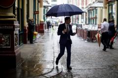 A businessman walks through the rain. (Photo credit: TOLGA AKMEN/AFP via Getty Images)