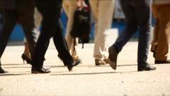Businessmen walk to work. (Photo credit: YouTube/Transformation Video Library)