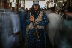A Taliban fighter stands guard as people move past him at a market with shops dealing with currency exchange in Kabul on September 5, 2021. (Photo by AAMIR QURESHI/AFP via Getty Images)