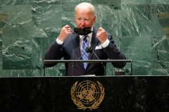 President Joe Biden takes off his protective facemask due to the coronavirus disease (Covid-19) pandemic as he arrives to speak at the 76th Session of the UN General Assembly on September 21, 2021 in New York. - The summit will feature the first speech to the world body by US President Joe Biden, who has described a rising and authoritarian China as the paramount challenge of the 21st century. (Photo by EDUARDO MUNOZ/POOL/AFP via Getty Images)