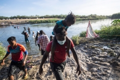 Haitian migrants cross the Rio Grande river to get food and water in Mexico, as seen from Ciudad Acuna, Coahuila state, Mexico on Sept. 22. (Photo credit: PEDRO PARDO/AFP via Getty Images)
