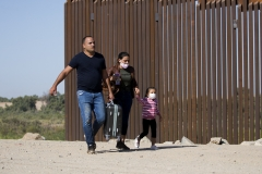 Migrants from Cuba walk along the border wall after crossing the United States and Mexico border, to turn themselves to authorities on May 13, 2021 in Yuma, Ariz. (Photo credit: RINGO CHIU/AFP via Getty Images)