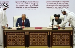 U.S. envoy for Afghanistan Zalmay Khalilzad and Abdul Ghani Baradar of the Taliban sign the agreement in Doha in February 2020. (Photo by Karim Jaafar/AFP via Getty Images)