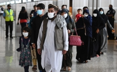Afghan evacuees arrive at Dulles International Airport near Washington, D.C., on August 27, 2021. (Photo by OLIVIER DOULIERY/AFP via Getty Images)