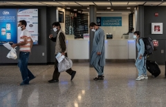 Afghan evacuees are escorted to a waiting bus after arriving at Dulles International Airport in Chantilly, Virginia on August 23, 2021. (Photo by ANDREW CABALLERO-REYNOLDS/AFP via Getty Images)