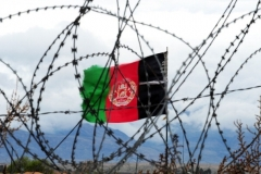 Afghanistan's national flag flies behind barbed wire at a military base in Nangarhar province in 2014.  (Photo by Roberto Schmidt/AFP via Getty Images)