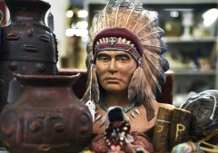 A plaster bust of an American Indian chief wearing a feather headdress or war bonnet is among items for sale in an antiques shop in Grants Pass, Ore. (Photo credit: Robert Alexander/Getty Images)