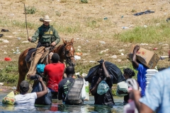 A Border Patrol agent on horseback uses the reins as he tries to stop Haitian migrants from entering an encampment on the banks of the Rio Grande near the Acuna Del Rio International Bridge in Del Rio, Tex. (Photo credit: PAUL RATJE/AFP via Getty Images)