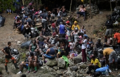 Haitian migrants rest as they cross the jungle of the Darien Gap, near Acandi, Choco department, Colombia, heading to Panama, on September 26, 2021, on their way trying to reach the US. - From Acandi, they started on foot -- and armed with machetes, lanterns and tents -- the dangerous trek of at least five days to Panama through the Darien jungle, battling snakes, steep ravines, swollen rivers, tropical downpours and criminals often linked to drug trafficking. (Photo by RAUL A