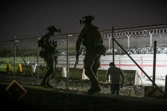 Coalition soldiers secure a section of perimeter fence at Kabul airport during the August evacuation mission. (Photo by Wakil Kohsar/AFP via Getty Images)