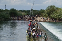 Migrants, many of them Haitian, cross the Rio Grande near Del Rio, Texas in September. (Photo by Paul Ratje/AFP via Getty Images)