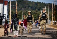US Military Police walk past Afghan refugees at the Ft. McCoy US Army base on September 30, 2021 in Ft. McCoy, Wisconsin. (Photo by BARBARA DAVIDSON/POOL/AFP via Getty Images)
