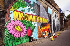 Street artists paint a mural on a wall opposite the COP26 climate summit venue in Glasgow on October 13, 2021. (Photo by ANDY BUCHANAN/AFP via Getty Images)