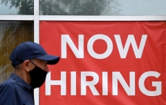 """A man walks by a """"Now Hiring"""" sign outside a store in Arlington, Virginia in August 2021. (Photo by OLIVIER DOULIERY/AFP via Getty Images)"""