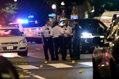 Police officers work at the scene of a shooting outside a restaurant in Washington, DC, on July 22, 2021.  (Photo by BRENDAN SMIALOWSKI/AFP via Getty Images)