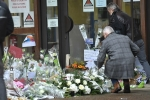 People leave flowers at the school in northwest Paris where teacher Samuel Paty was murdered. (Photo by Bertrand Guay/AFP via Getty Images)