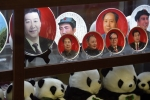 Images of President Xi Jinping and past CCP leaders are displayed above a row of pandas in a Beijing shop window. (Photo by Greg Baker/AFP via Getty Images)