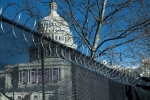 Razor wire is installed atop a security fence in preparation for the the most  heavily guarded presidential inauguration in history. (Photo by BRENDAN SMIALOWSKI/AFP via Getty Images)