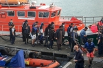 Illegal migrants plucked from a leaking inflatable boat in the Channel are escorted off a rescue vessel docked in Calais, northern France, last month. (Photo by Bernard Barron/AFP via Getty Images)