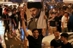 Supporters of Moqtada al-Sadr celebrate the interim election results in Baghdad's Tahrir square. (Photo by Ahmad al-Rubaye/AFP via Getty Images)